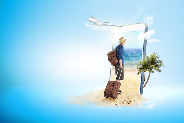 Widok z tyłu azjatycki człowiek w kapeluszu z walizką i plecak spacery na plażę Premium Zdjęcia