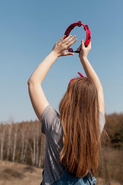 Widok Z Tyłu Beztroskiej Kobiety Bawiące Się Tamburyn W Przyrodzie Darmowe Zdjęcia