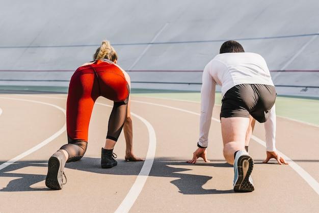 Widok z tyłu biegaczy zajmujących pozycję Darmowe Zdjęcia