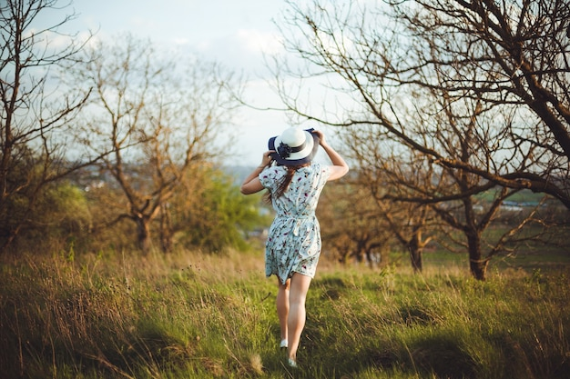 Widok Z Tyłu Całkiem Młoda Kobieta W Niebieskiej Sukience Trzyma Kapelusz Działa Spacery W Ogrodzie. Piękna Dziewczyna, Ciesząc Się Ogrodem Wczesną Wiosną, Relaks Na świeżym Powietrzu, Zabawę. Premium Zdjęcia