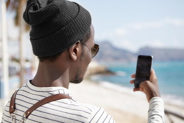 Widok Z Tyłu Czarnego Backpackera W Kapeluszu I Koszuli W Paski Z Widokiem Na Morze, Trzymając Smartfon I Robiąc Zdjęcia Pięknego Krajobrazu Podczas Swojej Podróży Darmowe Zdjęcia