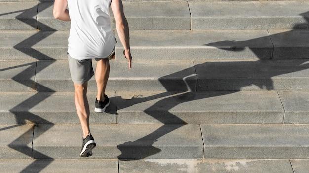 Widok Z Tyłu Człowiek Działa Na Schodach Z Miejsca Kopiowania Darmowe Zdjęcia