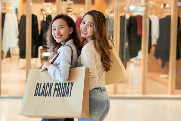 Widok z tyłu dwóch pań, które robią zakupy w czarny piątek, odwracając się, by spojrzeć na kamerę Darmowe Zdjęcia