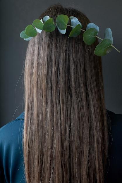 Widok z tyłu gałęzi eukaliptusa jak korona na włosach dziewczyny z brązowymi włosami na ciemnym tle Premium Zdjęcia