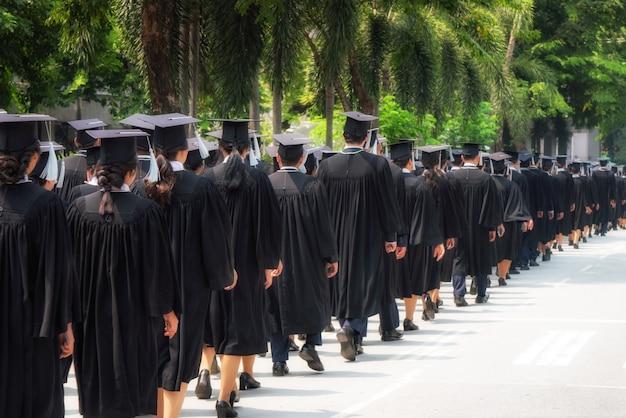 Widok Z Tyłu Grupy Absolwentów Uniwersytetów W Czarnych Sukniach Ustawia Się W Kolejce Po Dyplom Ukończenia Uniwersytetu. Premium Zdjęcia