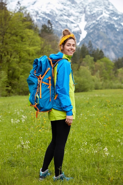 Widok Z Tyłu Kobiecej Turystki Spacerującej Na Nogach Na Zielonej łące Na Tle Górskiego Krajobrazu, Nosi Duży Plecak Darmowe Zdjęcia