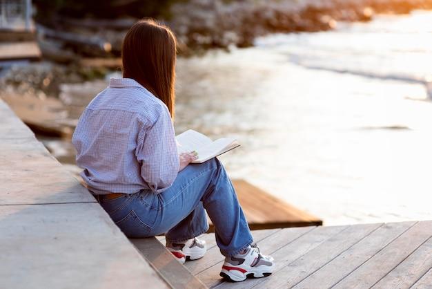 Widok Z Tyłu Kobieta Trzyma Książkę Z Miejsca Na Kopię Premium Zdjęcia