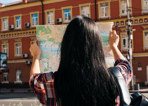 Widok z tyłu kobiety czytania mapy z tłem czerwonej zewnętrznej budynku Darmowe Zdjęcia