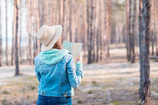 Widok z tyłu kobiety na sobie kapelusz, patrząc na mapę w lesie Darmowe Zdjęcia
