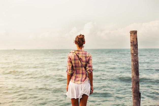 Widok z tyłu kobiety patrząc na morze Darmowe Zdjęcia