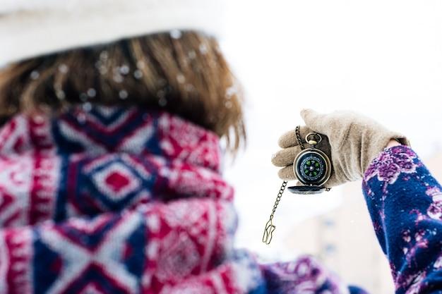 Widok Z Tyłu Kobiety Trzymającej Kompas W środku Burzy śnieżnej. Premium Zdjęcia