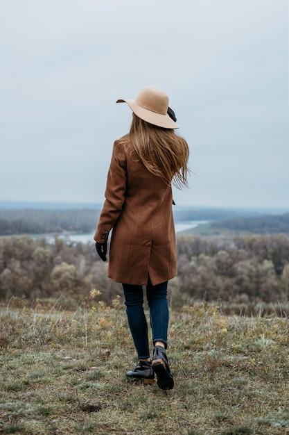 Widok Z Tyłu Kobiety W Kapeluszu Pozowanie W Przyrodzie Na Zewnątrz Darmowe Zdjęcia