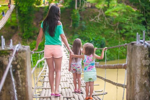Widok z tyłu małych dziewczynek i młodej kobiety chodzenie na most wiszący nad rzeką loboc, filipiny Premium Zdjęcia