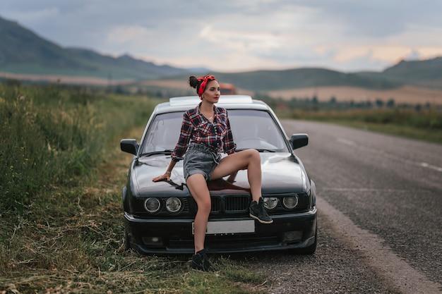 Widok z tyłu młodej dziewczyny w szarych krótkich spodenkach jeansowych naprawia samochód. w szortach w pobliżu czarnego samochodu z otwartą maską. problemy z samochodem podczas podróży. brunetka naprawia silnik Premium Zdjęcia