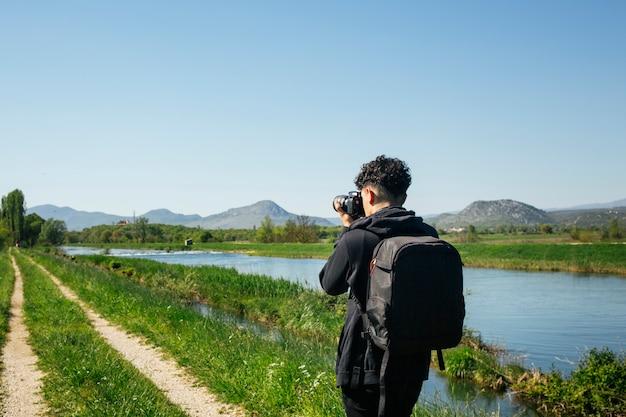 Widok z tyłu młody fotograf biorąc zdjęcie płynącej rzeki Darmowe Zdjęcia