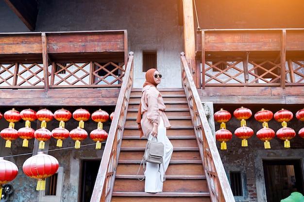 Widok Z Tyłu Muzułmańskiej Kobiety Turystycznej Stojącej Na Schodach W Chińskiej Domowej Atmosferze, Azjatyckie Kobiety W Wakacje. Koncepcja Podróży. Motyw Chiński. Premium Zdjęcia