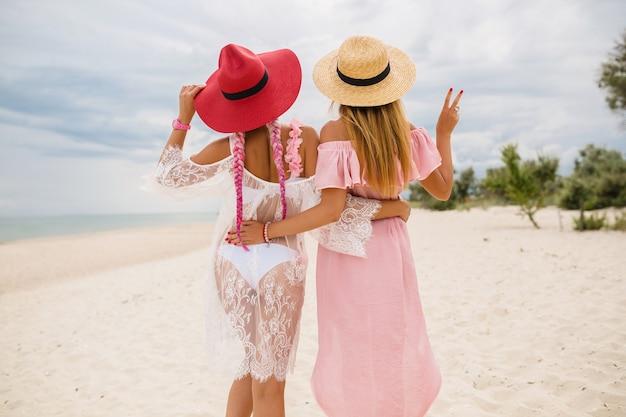 Widok Z Tyłu Na Dwie Piękne Stylowe Kobiety Na Plaży Na Wakacjach, Letni Styl, Trend W Modzie, Noszenie Słomkowych Kapeluszy, Trend W Modzie, Różowa I Koronkowa Sukienka, Seksowny Strój Darmowe Zdjęcia