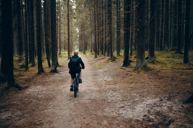 Widok Z Tyłu Nierozpoznawalnego Mężczyzny Jadącego Na Rowerze Górskim Wzdłuż Opuszczonej ścieżki W Lesie. Tylne Ujęcie Mężczyzny Na Rowerze W Lesie W Spokojny Poranek Bez Nikogo W Pobliżu. Koncepcja Ludzi, Przyrody I Sportu Darmowe Zdjęcia