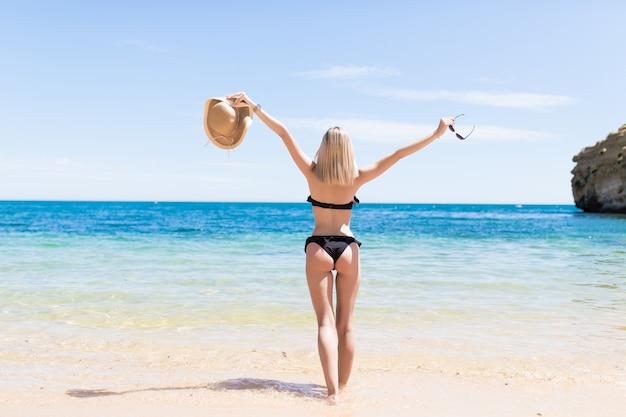 Widok Z Tyłu Piękna Młoda Kobieta Podniosła Ręce Na Plaży Darmowe Zdjęcia