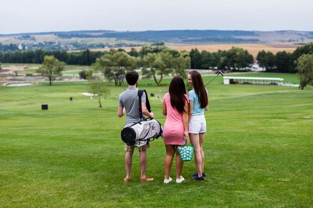 Widok z tyłu przyjaciół na polu golfowym Darmowe Zdjęcia