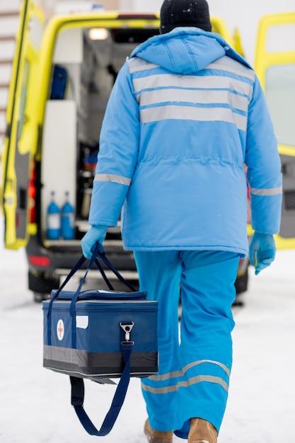 Widok Z Tyłu Ratownika Medycznego W Niebieskiej Odzieży Roboczej I Rękawiczkach Medycznych Niosącego Apteczkę W Drodze Do Samochodu Pogotowia Ratunkowego Premium Zdjęcia