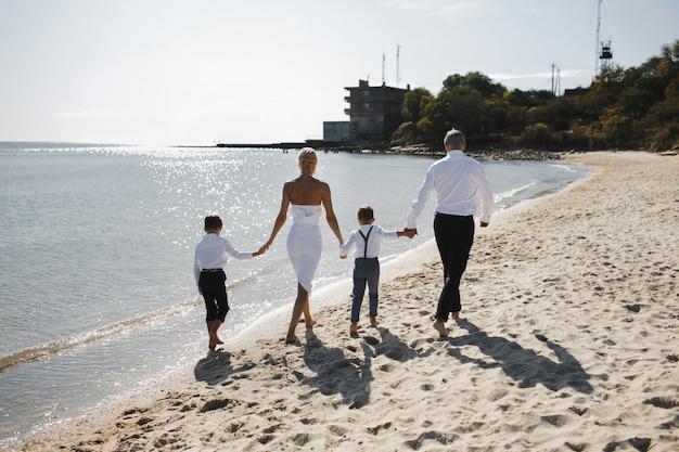 Widok Z Tyłu Rodziców I Dzieci Trzymają Się Za Ręce I Spacerują Po Plaży W Słoneczny Letni Dzień, Ubrani W Białe Stylowe Ubrania Darmowe Zdjęcia