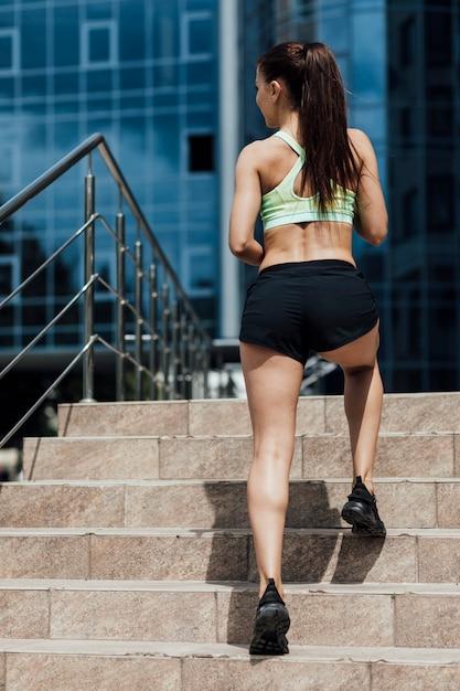 Widok z tyłu sportowca działa na schodach Darmowe Zdjęcia