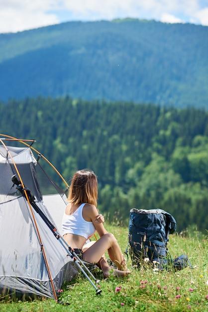 Widok Z Tyłu Sportowy Młodych Kobiet Arywista Siedzi Przy Wejściu Do Namiotu Obok Plecaka I Kije Trekkingowe, Ciesząc Się Słoneczny Poranek W Górach. Koncepcja Stylu życia Premium Zdjęcia