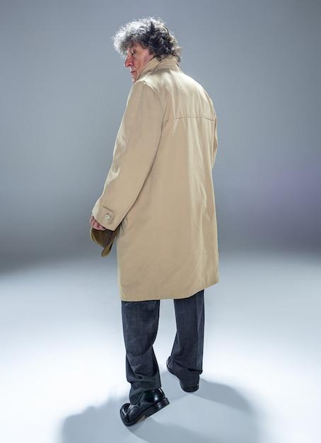 Widok Z Tyłu Starszy Mężczyzna W Płaszczu Jako Szef Detektywa Lub Mafii. Studio Strzałów Na Szaro W Stylu Retro. Dojrzały Mężczyzna Z Kapeluszem I Walizką Darmowe Zdjęcia
