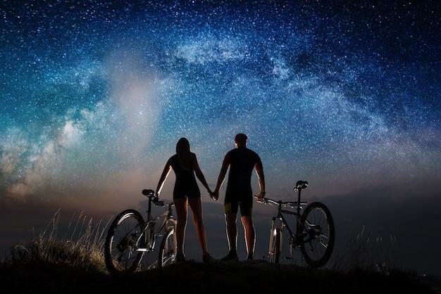 Widok z tyłu sylwetka rowerzystów para trzymając się za ręce, ciesząc się noc gwiaździste niebo. Premium Zdjęcia