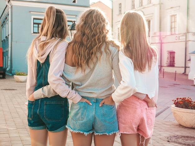 Widok Z Tyłu Trzech Młodych Przyjaciółek Hipster. Dziewczyny Ubrane W Letnie Ubrania Casualowe. Kobiety Stojące Na Zewnątrz. Wkładają Ręce W Szorty W Tylnych Kieszeniach. Pozowanie O Zachodzie Słońca Darmowe Zdjęcia