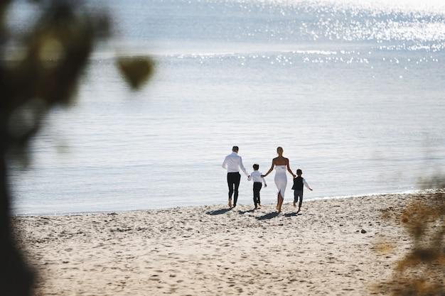 Widok Z Tyłu Z Systemem Rodziny Na Plaży W Słoneczny Dzień W Pobliżu Morza Ubrany W Modne Ubrania Darmowe Zdjęcia