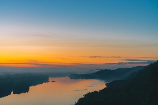 Widok z wysokiego brzegu na rzece. brzeg rzeki z lasem pod gęstą mgłą. złoty świt odbity w wodzie. żółty blask w malowniczym niebie przedświtu. kolorowego poranka nastrojowy krajobraz o majestatycznej naturze. Premium Zdjęcia
