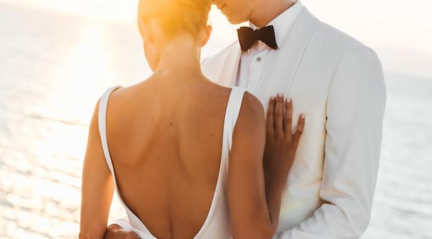 Wieczorne słońce świeci na piękny ślub para przytulanie przed morzem Darmowe Zdjęcia