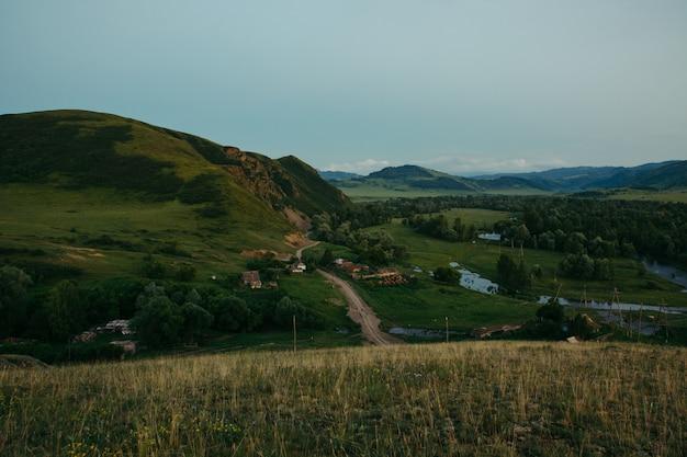 Wieczorny Krajobraz Wsi Zbudowany Wśród Wzgórz, Lasów I Gór. Otwarta Przestrzeń. Dzika Natura. Interakcja Z Naturą Ałtaju. Premium Zdjęcia