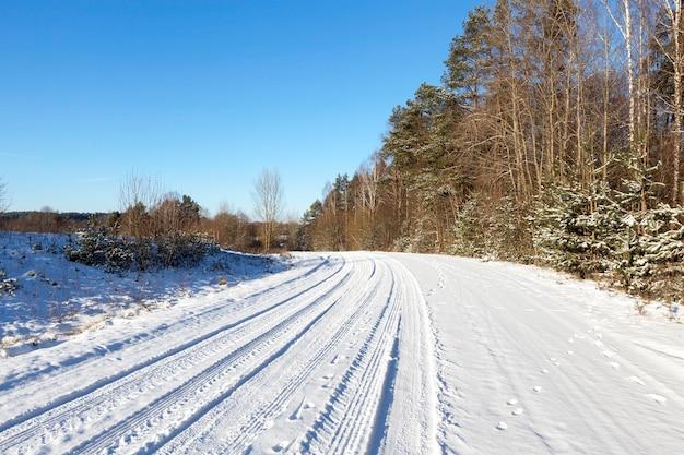 Wiejska Droga Pokryta śniegiem Zimą. Na Drzewach Przydrożnych. Na śniegu Widoczne Odciski Palców Z Opon Samochodowych I Zabójczej Przyrody. Sfotografowany Z Bliska. Premium Zdjęcia