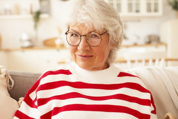 Wiek, Ludzie Dojrzali, Styl życia I Koncepcja Emerytury. Bliska Strzał Szczęśliwej Uroczej Starszej Kobiety Na Emeryturze Na Sobie Stylową Bluzę W Paski I Okulary Relaks W Domu, Uśmiechając Się Radośnie Darmowe Zdjęcia
