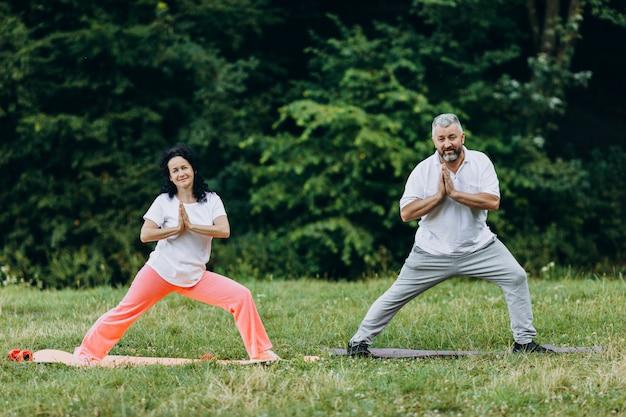 Wiek średni para robi joga stoi i robi gestowi namaste joga Premium Zdjęcia