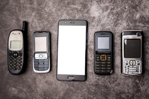 Wiele Przestarzałych Telefonów Komórkowych I Smartfona Na Tle Grunge. Premium Zdjęcia