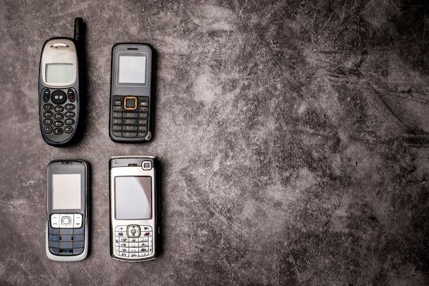 Wiele Przestarzałych Telefonów Komórkowych Na Tle Grunge. Premium Zdjęcia