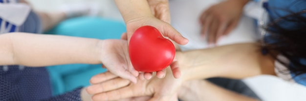 Wiele Rąk Kobiet, Mężczyzn I Dzieci, Jedna Nad Drugą, Trzyma Serce. Premium Zdjęcia