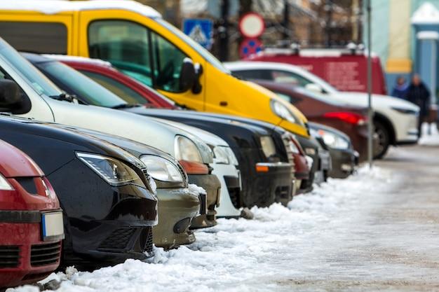 Wiele różnych samochodów zaparkowanych w mieście. samochody na sprzedaż Premium Zdjęcia