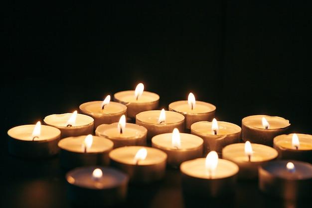 Wiele świec Płonących W Nocy. Wiele Płomieni świec świecące Na Ciemnym Tle Premium Zdjęcia