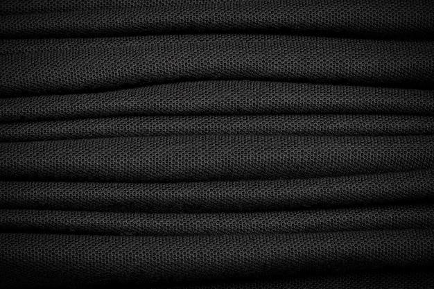 Wiele tła czarnej koszuli. ciemny materiał tekstylny. Premium Zdjęcia