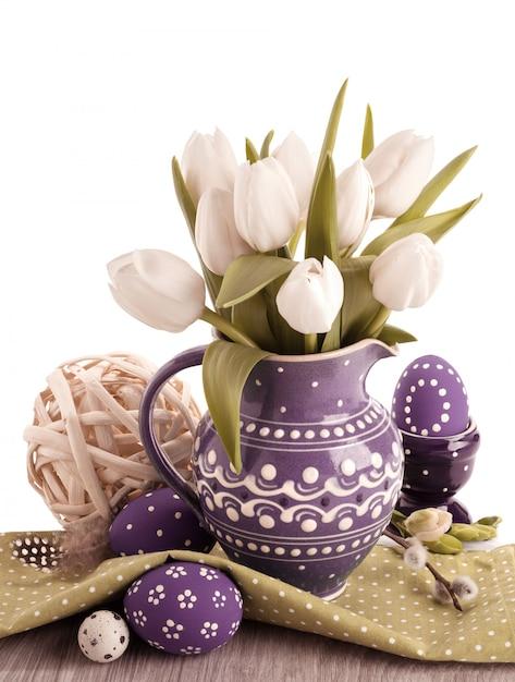 Wielkanoc z białymi tulipanami w fioletowym dzbanku i pasującymi pisankami Premium Zdjęcia