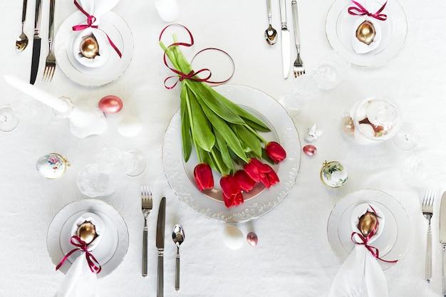 Wielkanocna świąteczna Wiosna Nakrycia Stołu Dekoracja, Jajka W Gnieździe, świeże Czerwone Tulipany Premium Zdjęcia