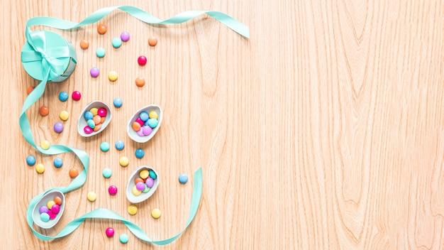 Wielkanocne Jajka Czekoladowe Na Tle Drewna Z Kolorowe Cukierki Bonbon, Wstążki, Pudełka. świąteczna Koncepcja, Miejsce Premium Zdjęcia