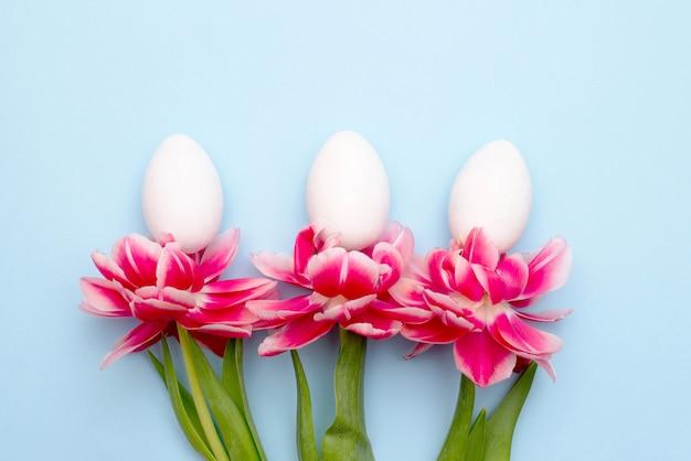 Wielkanocni Biali Jajka I Wiosen Różowi Kwiaty Z Kopii Przestrzenią. Premium Zdjęcia