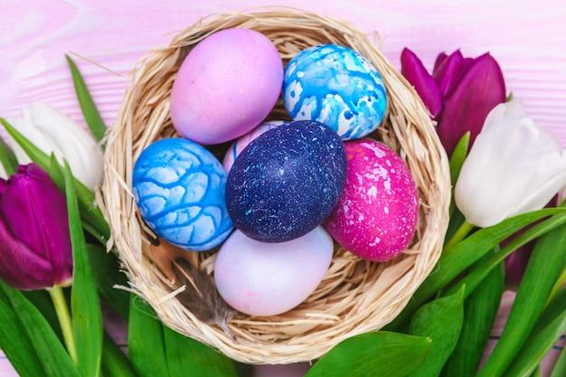 Wielkanocni jajka w gniazdeczku i tulipanach na drewnianych deskach Premium Zdjęcia