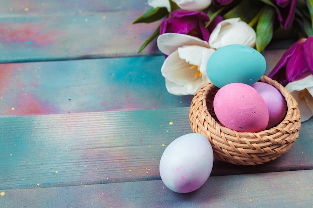 Wielkanocni Jajka Z Tulipanami Na Błękitnym Drewnianym Stole Premium Zdjęcia